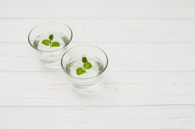 Woda z miętą w szkłach na stole