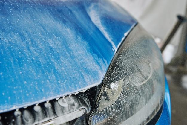 Woda z mydłem spływająca z umytego niebieskiego samochodu myjącego z bezdotykowym myciem pod wysokim ciśnieniem