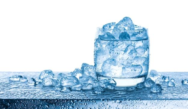 Woda z zdruzgotanymi kostkami lodu w szkle na białym tle