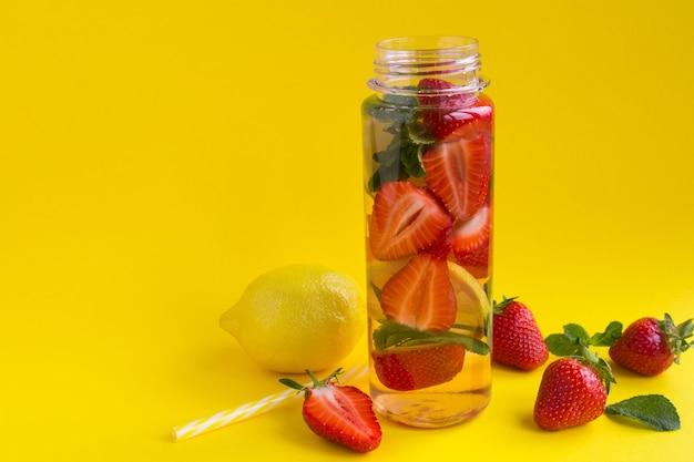 Woda zaparzona lub oczyszczająca z truskawek i cytryny w butelce