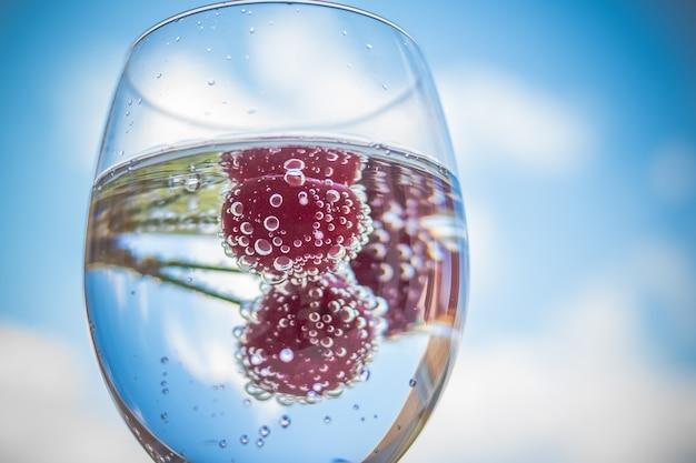 Woda ze świeżymi owocami i szklanymi naczyniami. koktajle z dojrzałą słodką czerwoną wiśnią. lemoniada, letnie napoje. szklanka wody lodowej lemoniady