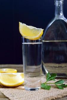 Wódka lub tequila w kieliszkach i butelce z cytryną