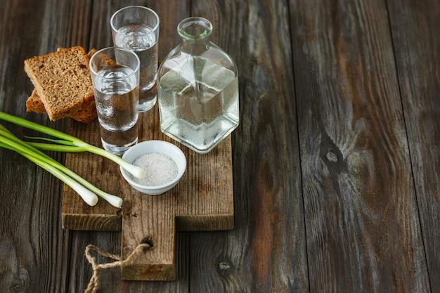 Wódka z zieloną cebulą, tostami chleba i solą na podłoże drewniane. czysty alkoholowy napój rzemieślniczy i tradycyjna przekąska. negatywna przestrzeń. świętując jedzenie i pyszne.