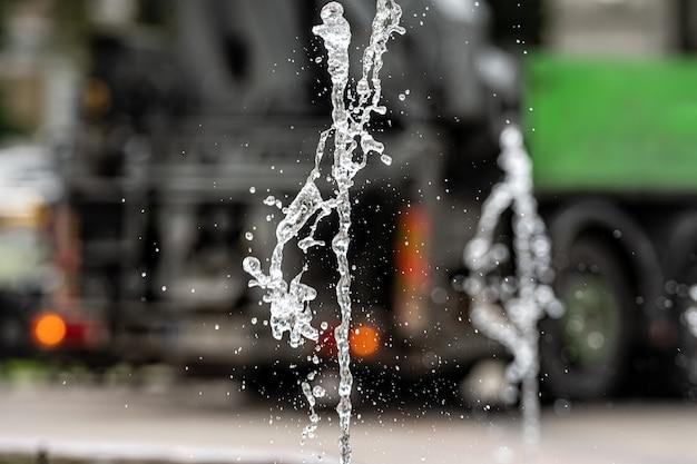 Wodna fontanna bryzga na niewyraźnej ulicy