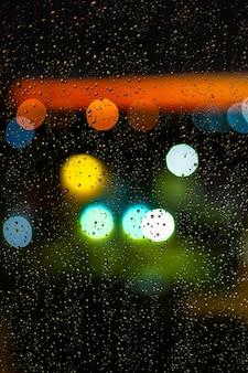 Wodna kropla przy okno i bokeh miasto w zmierzchu