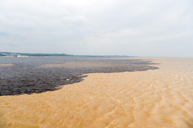 Wodne spotkanie w brazylii - amazonka z rio del negro czysta i brudna woda w rzece z różnymi strumieniami