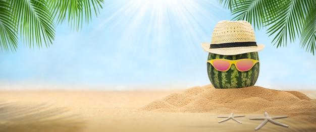 Wodny melon z kapeluszem, pusty piasek z kapeluszem i napojem mojito na krajobrazowej plaży rozmazane tło