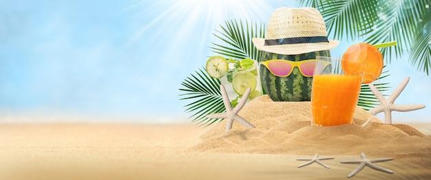 Wodny melon z kapeluszem, pusty piasek z kapeluszem i napojem owocowym na krajobrazowej plaży rozmazane tło