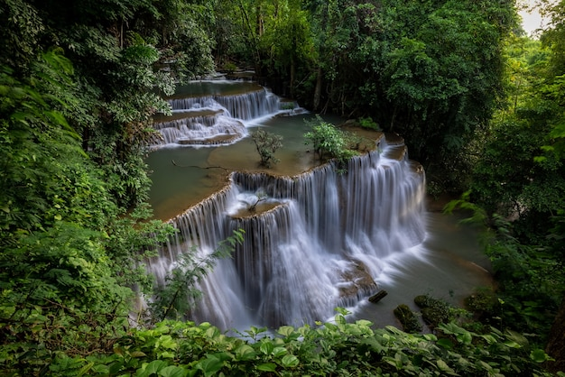 Wodospad hua mea khamin ma tropikalne drzewa, paprocie, rosnące rano na wodospadzie