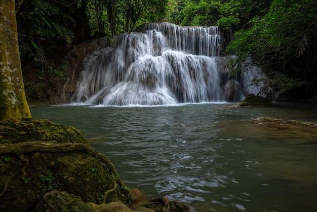 Wodospad hua mea khamin to tropikalne drzewa, paprocie, poranny wzrost na wodospadzie w porannym świetle, chłodna, świeża pogoda i ciche miejsce na relaks w dżungli. karnchanaburi, tajlandia.