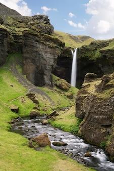 Wodospad kvernufoss, islandia. piękna kaskada wody w zielonym wąwozie. letni krajobraz z górską rzeką i skałami