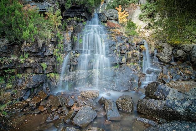 Wodospad o niebieskich odcieniach, z zieloną roślinnością, w czarnej lagunie soria w hiszpanii