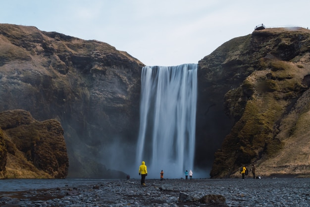 Wodospad skogafoss otoczony ludźmi i skałami pod zachmurzonym niebem na islandii