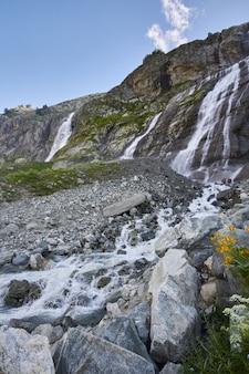 Wodospad w górach kaukazu, topniejący grzbiet lodowca arkhyz, wodospady sofii. piękne wysokie góry rosji