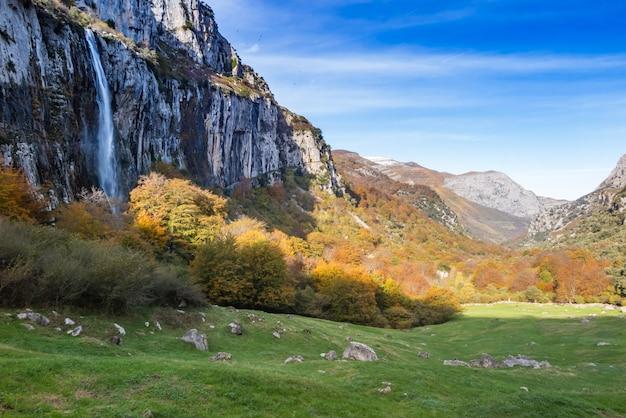 Wodospad w góry spadają na las jesienią