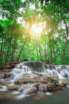 Wodospad w lesie deszczowym w zachodniej tajlandii z pomarańczowym światłem słonecznym w tle. robienie zdjęć z długimi czasami otwarcia migawki. wodospad huai mae khamin, prowincja kanchanaburi.