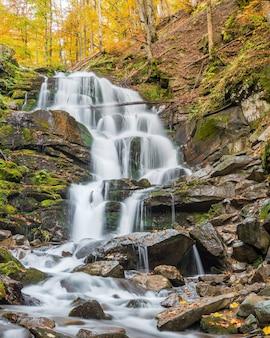 Wodospad w lesie z zielonymi liśćmi