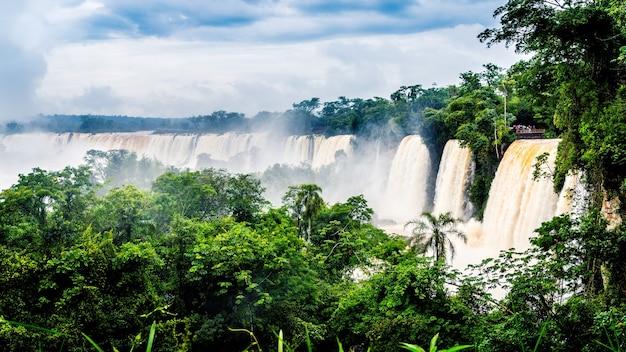 Wodospad w parku narodowym iguazu otoczony lasami pokrytymi mgłą pod zachmurzonym niebem