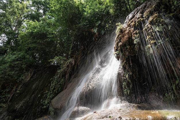 Wodospad w tropikalnym lesie deszczowym ze skałą i światłem słonecznym. wodospad saiyok noi, położony w prowincji kanchanaburi w tajlandii.