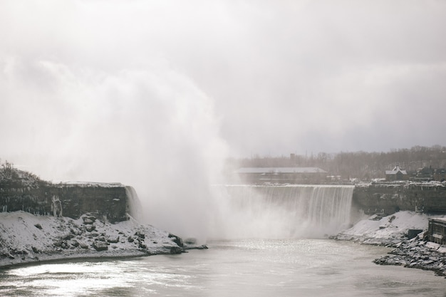 Wodospad w zimie z drzewami w tle w niagara falls w ontario w kanadzie