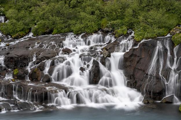 Wodospady hraunfossar otoczone zielenią w ciągu dnia na islandii