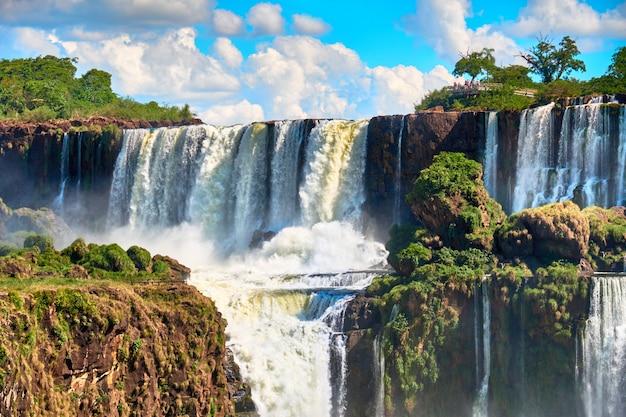 Wodospady iguazu w argentynie, widok z usta diabła. panoramiczny widok wielu majestatycznych potężnych kaskad wodnych tworzących mgłę nad rzeką iguazu. dolina z bujnym podzwrotnikowym lasem.