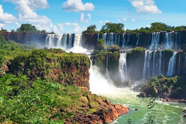 Wodospady iguazu w argentynie, widok z usta diabła. panoramiczny widok wielu majestatycznych potężnych kaskad wodnych tworzących mgłę nad rzeką iguazu przechodzącą przez subtropikalne liście w dolinie.
