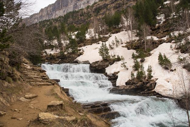 Wodospady rzeki arazas w parku ordesa naional ze śniegiem.
