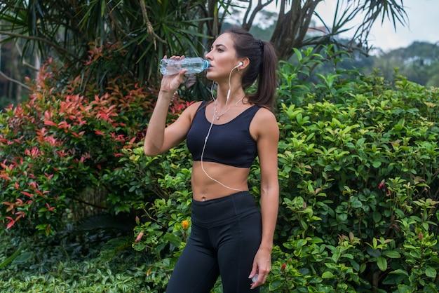 Wody pitnej szczupła dziewczyna sportowy. sprawności fizycznej młoda kobieta bierze przerwę po trenować w parku.