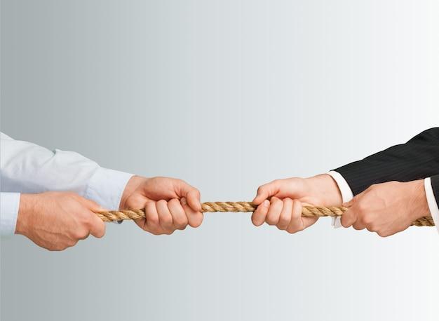 Wojna holowników, dwóch biznesmenów ciągnie linę w przeciwnych kierunkach