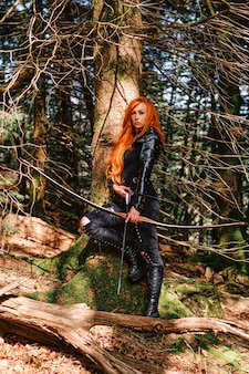 Wojownicza średniowieczna kobieta z polowaniem na łuk w tajemniczym lesie