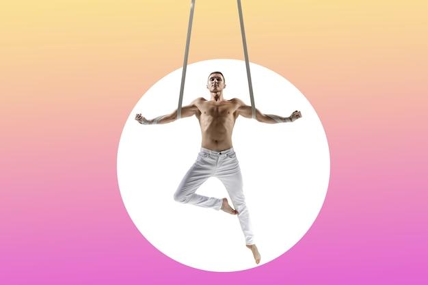 Wojownik. młody mężczyzna akrobata, sportowiec cyrkowy na białym tle na tle białego studia. trening doskonale wyważony w locie, artysta gimnastyki artystycznej ćwiczący ze sprzętem. gracja w wykonaniu.