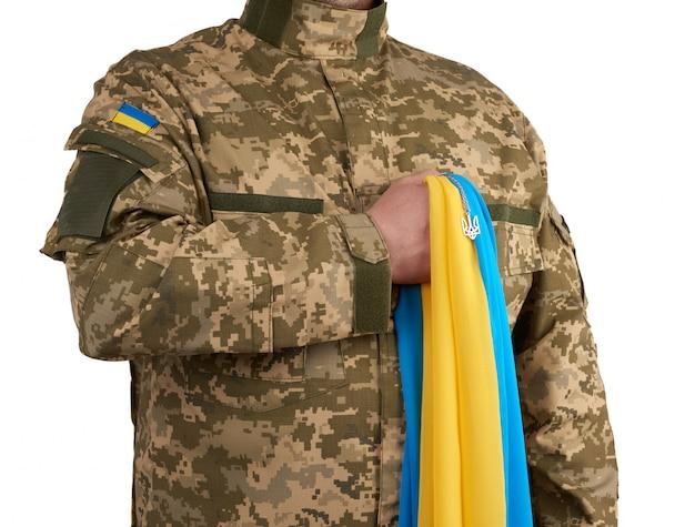 Wojownik ukraiński ubrany w wojskowy mundur pikselowy trzyma żółto-niebieską flagę państwa ukraińskiego