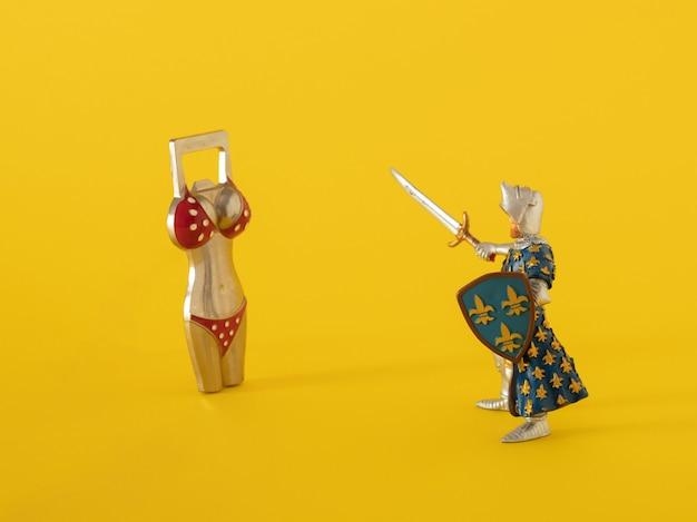 Wojownik zabawka z mieczem przeciwko otwieraczem do butelek na żółtym tle. streszczenie sztuka nowoczesna sztuka.