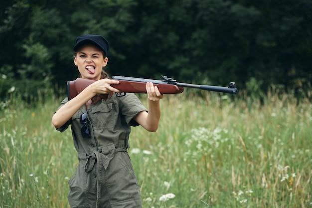 Wojskowa kobieta pokazuje język z bronią w dłoniach w zielonym kombinezonie, czarnej czapce, zielone drzewa w przestrzeni