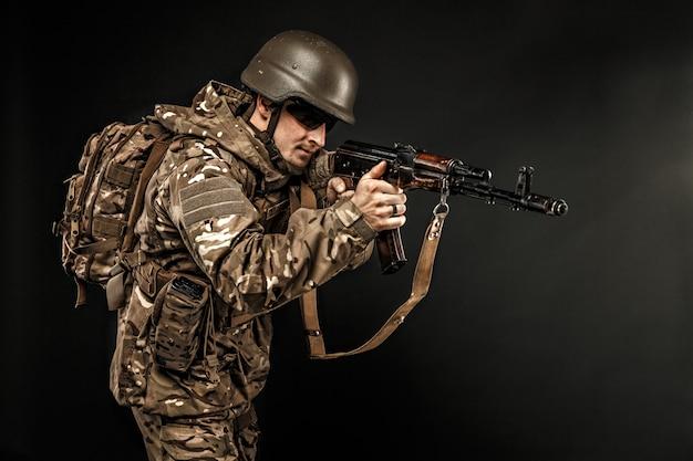 Wojskowy mężczyzna w mundurze celowania z pistoletu