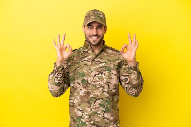 Wojskowy na białym tle na żółtym tle pokazujący znak ok palcami