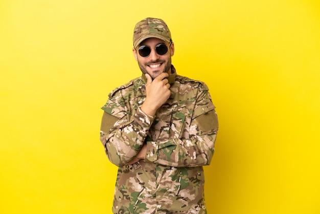 Wojskowy na białym tle na żółtym tle w okularach i uśmiechnięty