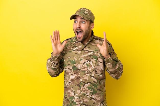 Wojskowy na białym tle na żółtym tle z niespodzianką wyrazem twarzy