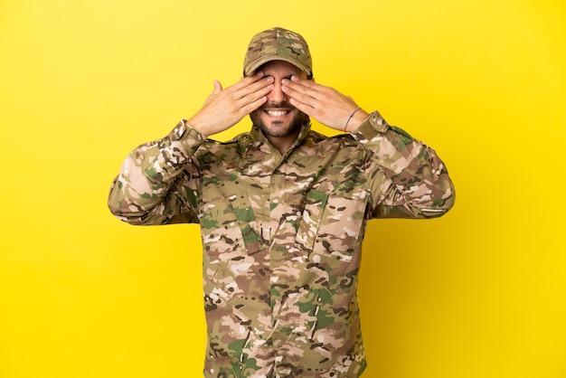 Wojskowy na białym tle na żółtym tle zakrywający oczy rękami