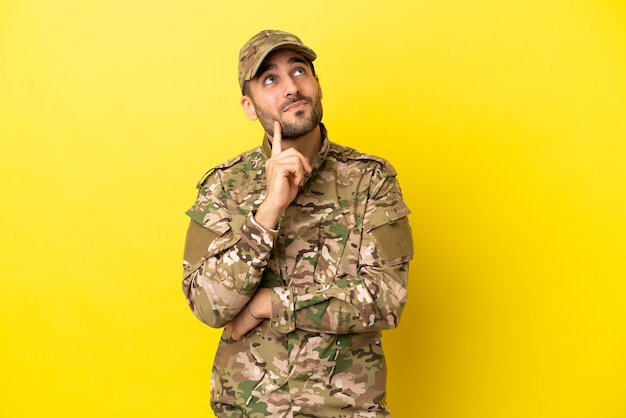 Wojskowy odizolowany na żółtym tle myślący o pomyśle, patrząc w górę