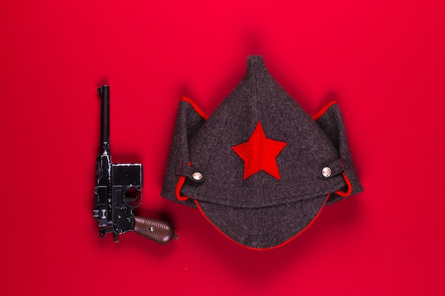 Wojskowy sowiecki wełniany kapelusz i pistolet na czerwonym tle
