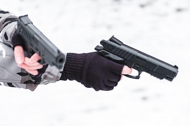 Wojskowy w kamuflażu i rękawice celujące z dwóch pistoletów.