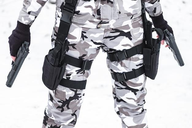 Wojskowy w kamuflażu i rękawiczkach trzyma dwa pistolety.