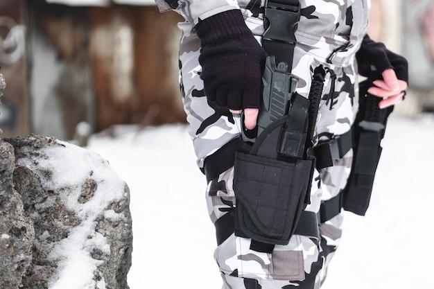 Wojskowy w kamuflażu i rękawiczkach wyjmuje pistolet z kabury.