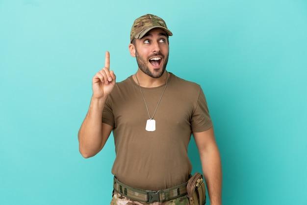 Wojskowy z nieśmiertelnikiem na białym tle na niebieskim tle, który zamierza zrealizować rozwiązanie, podnosząc palec w górę