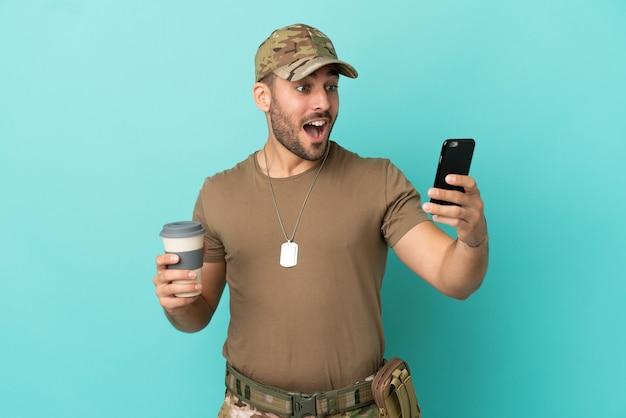 Wojskowy z nieśmiertelnikiem na białym tle na niebieskim tle, trzymający kawę na wynos i telefon komórkowy