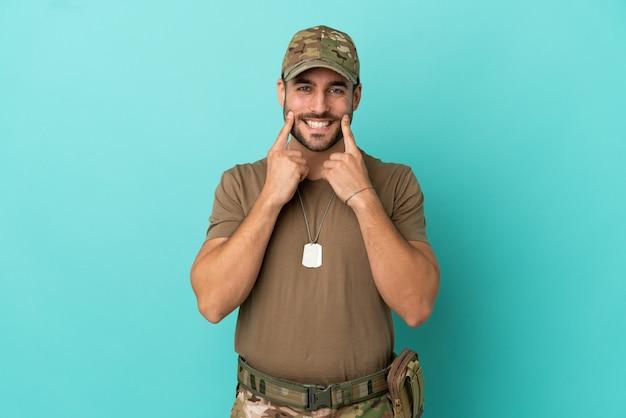 Wojskowy z nieśmiertelnikiem na białym tle na niebieskim tle uśmiechający się ze szczęśliwym i przyjemnym wyrazem twarzy