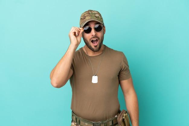Wojskowy z nieśmiertelnikiem na białym tle na niebieskim tle w okularach i zaskoczony