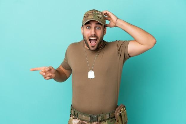Wojskowy z nieśmiertelnikiem na białym tle na niebieskim tle zaskoczony i wskazujący palcem na bok